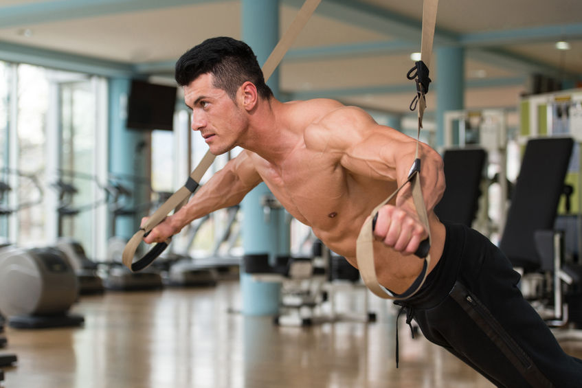 44727602 - attractive man does crossfit push ups with trx fitness straps in the gym's studio