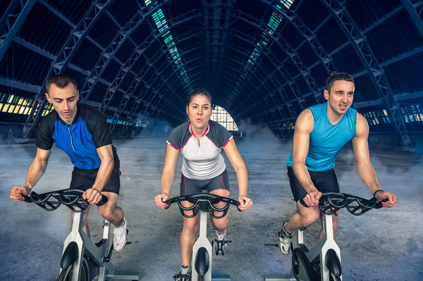38595976 - group of three people exercise on bike, spinning class,