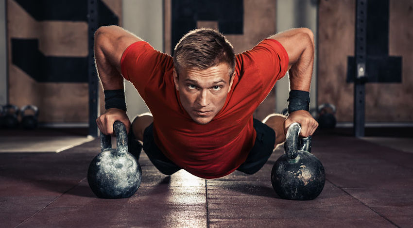 66436878 - handsome muscular man doing push ups on kettle ball in  gym